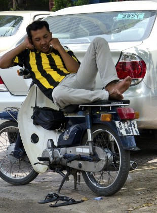 talking and riding; a moped driver in Phnom Penh, Camboja
