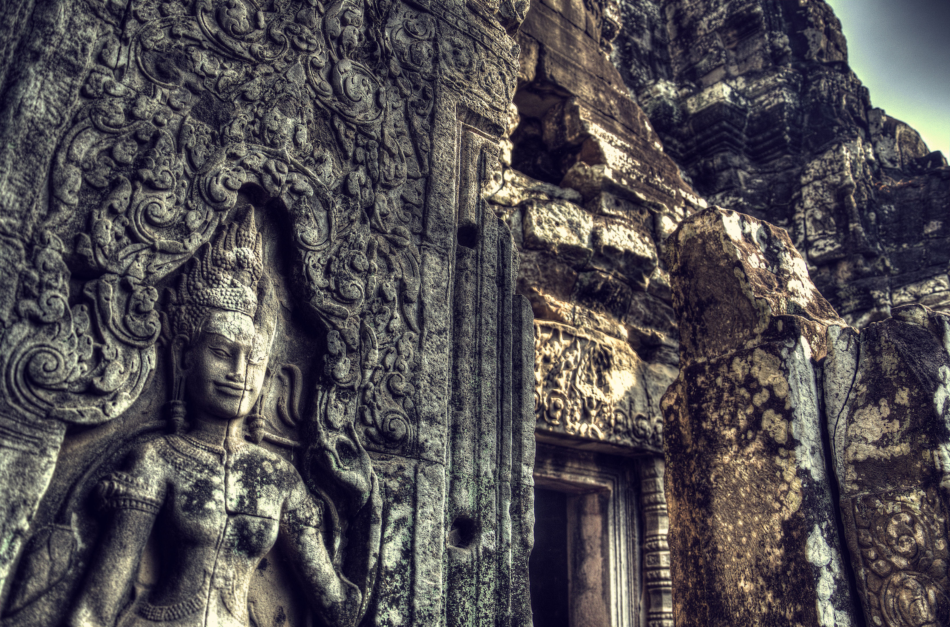 A carved sandstone apsara gazes down upon the millenia of ruin around her at the Bayon, Siem Reap.
