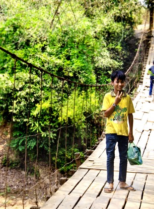 Kreung boy on swinging rope bridge