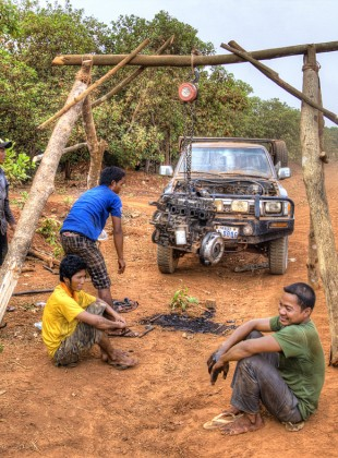 taking apart an engine by the side of the road in ratanakiri.