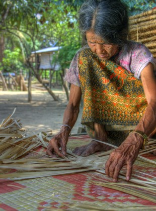 Hilltribe Brao woman weaving a sleeping mat by hand